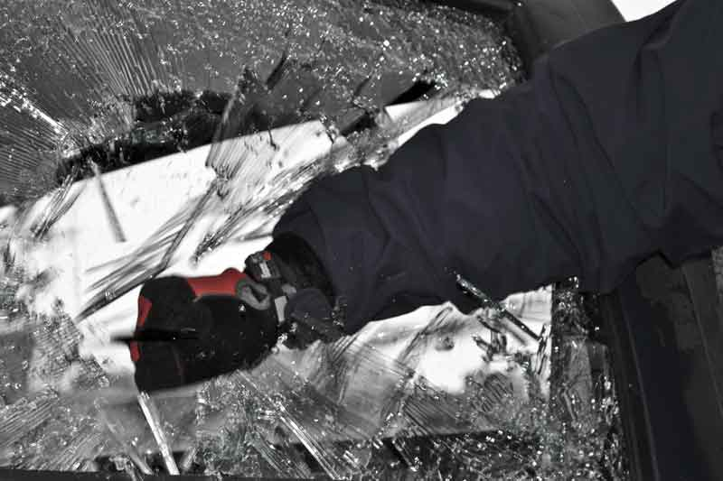 A photograph of a Shark Tooth Tactical knife breaking auto glass with the pommel tool.